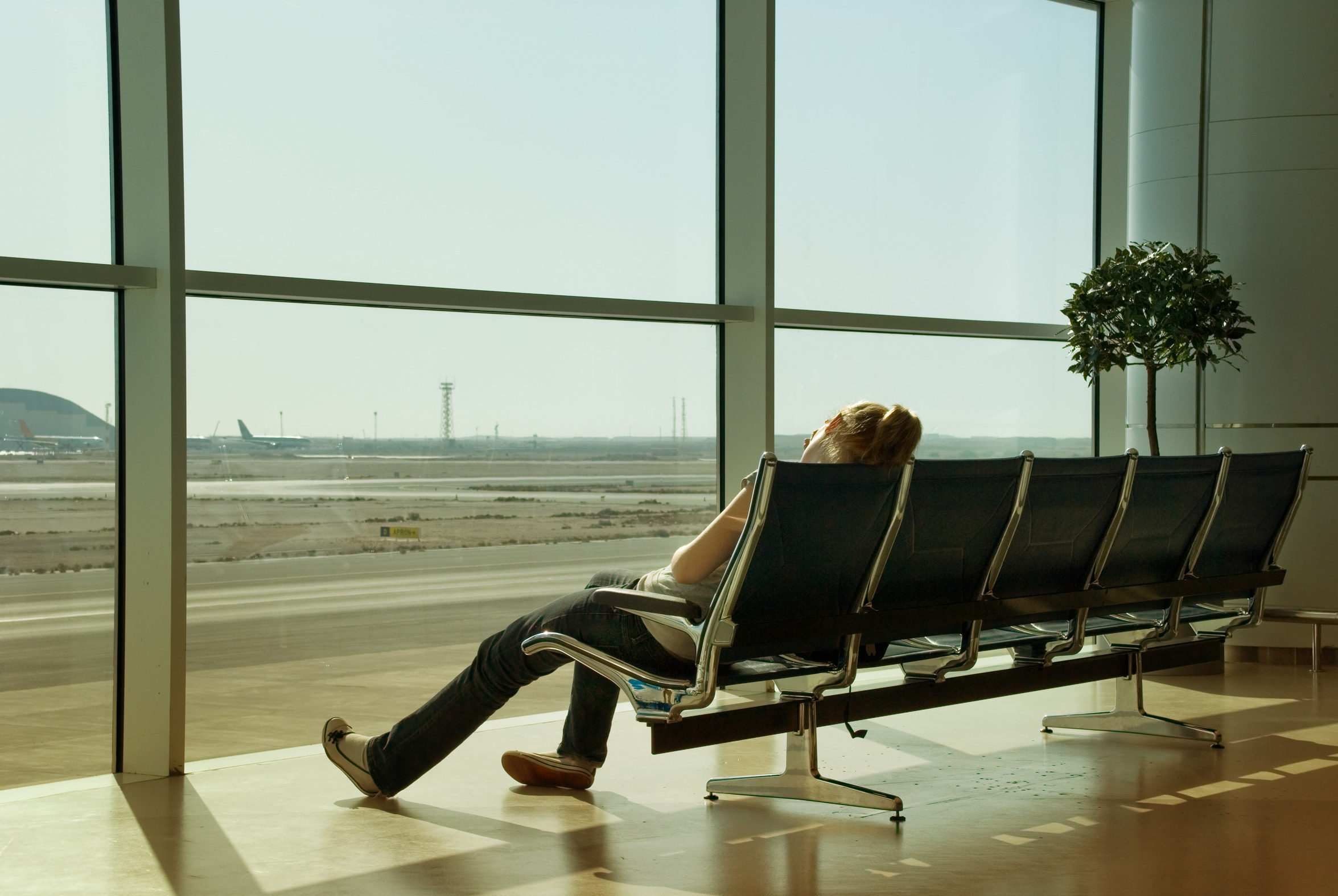 A lonely and jetlagged girl sitting and sleeping in a seats row in front of a sunny window facing the tarmac and airplanes on an airport passenger lounge.